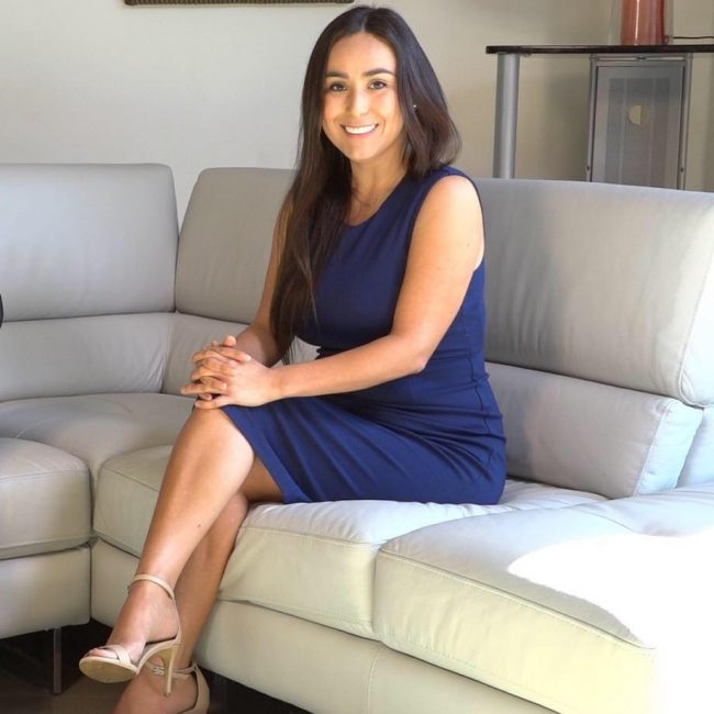 Adelia Carrillo sitting on a couch wearing a blue dress