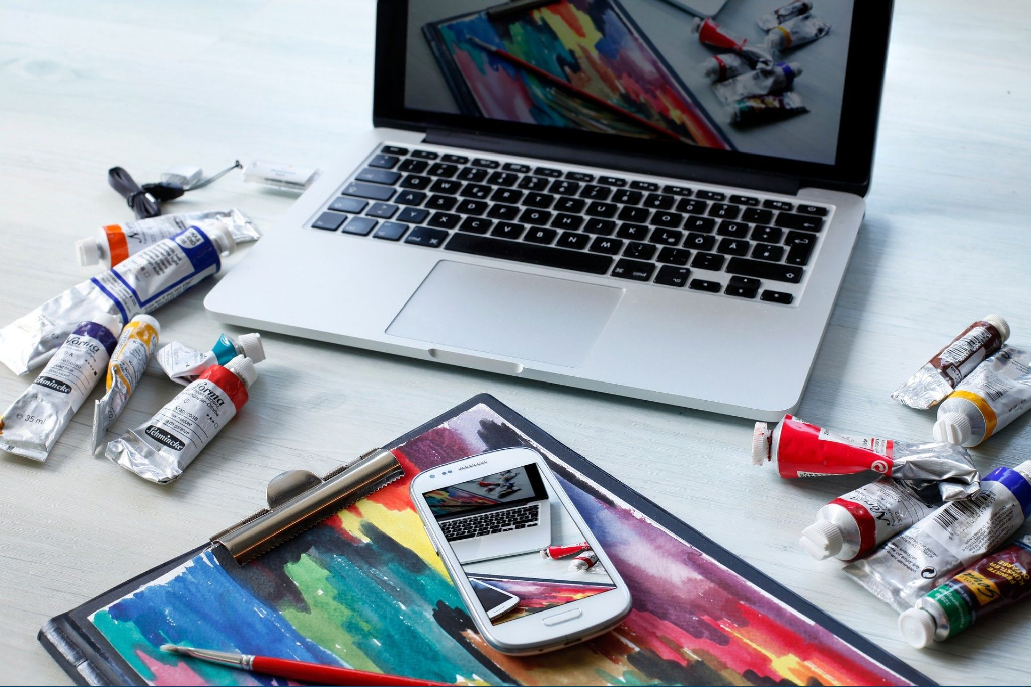 getting-creative-with-marketing-to-grow-your-cannabis-business-featured-blog-post-image-laptop-surrounded-by-tubes-of-paint